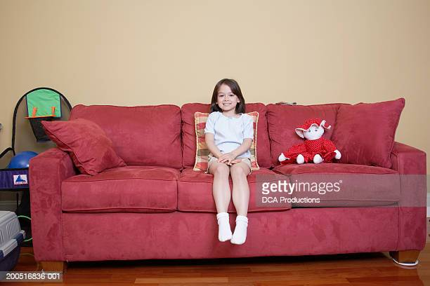 girl (5-7) sitting on sofa with stuffed toy, portrait - little girls socks stock photos and pictures
