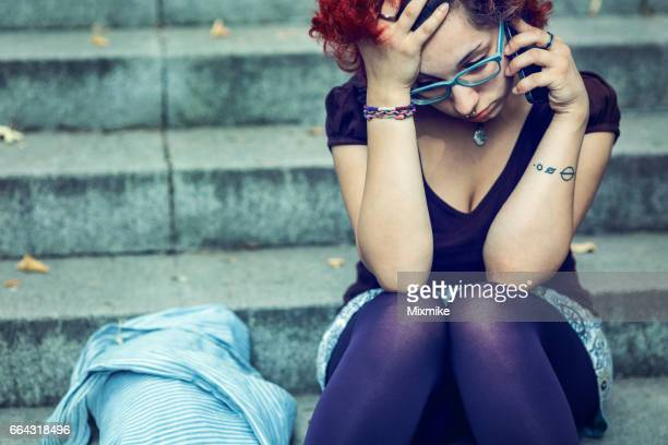 girl sitting on stairs and talking on the phone