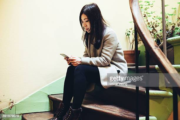 girl sitting on stairs and using smart phone - {{relatedsearchurl('london eye')}} stock photos and pictures