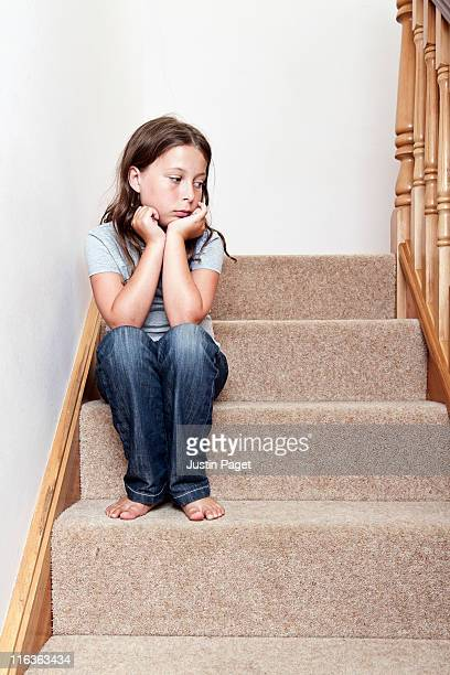 Girl (8-9) sitting on stairs