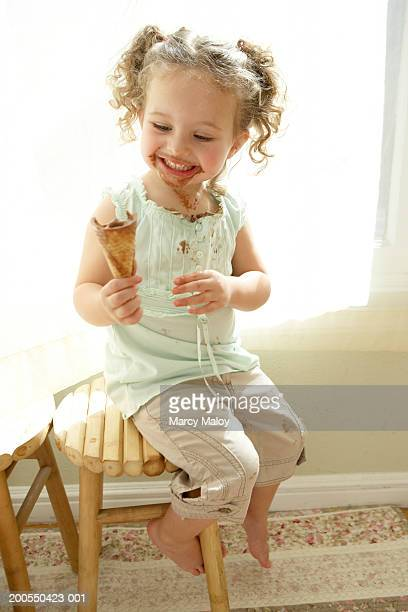 Girl (2-4) sitting on stool, eating ice cream cone, smiling