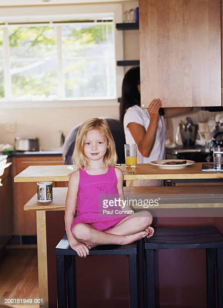 Girl (4-6) sitting on stool in kitchen, mom looking in cabinet behind