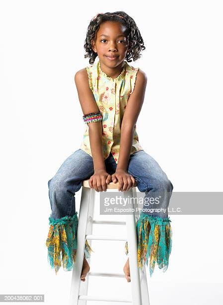 Girl (6-8) sitting on stool, portrait