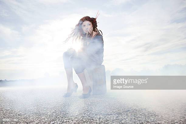 Girl sitting on suitcase in cloud of smoke