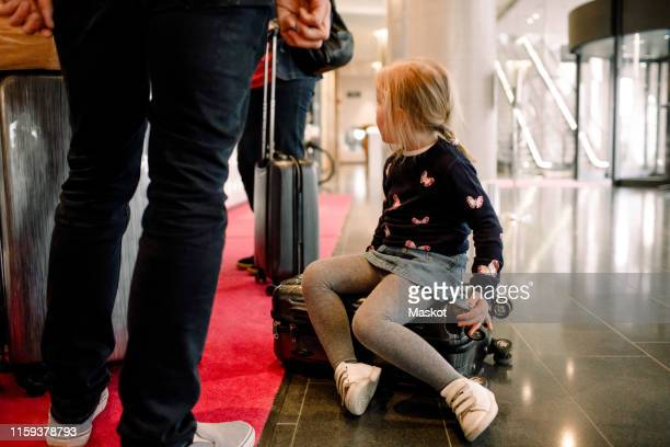 girl sitting on suitcase with family standing at reception in hotel - low section stock pictures, royalty-free photos & images