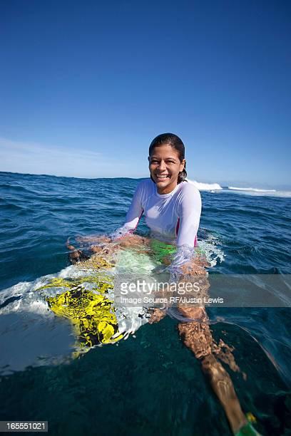 Girl sitting on surfboard in water