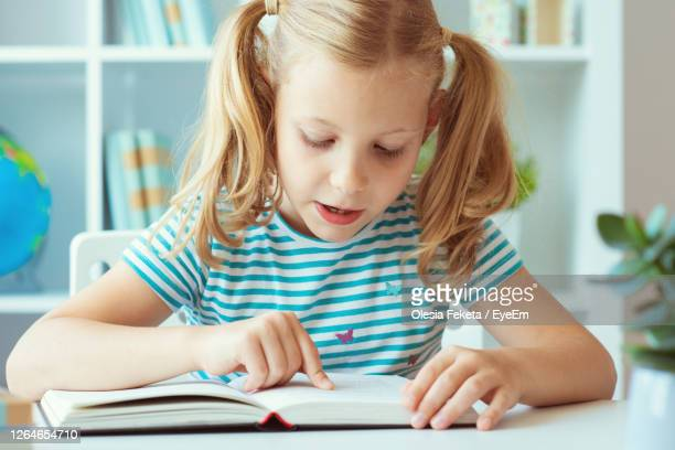 girl sitting on table - literature stock pictures, royalty-free photos & images