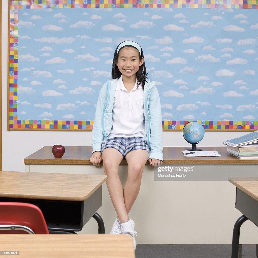 Girl sitting on teachers desk in classroom : Stock Photo