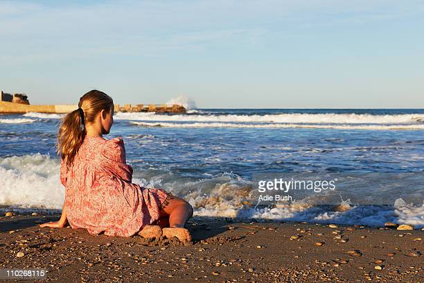 Girl sitting on the beach looking at sea