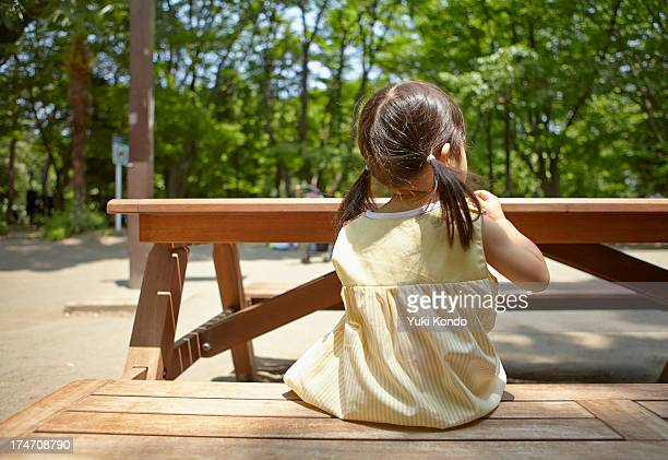 A girl sitting on the bench of a park.