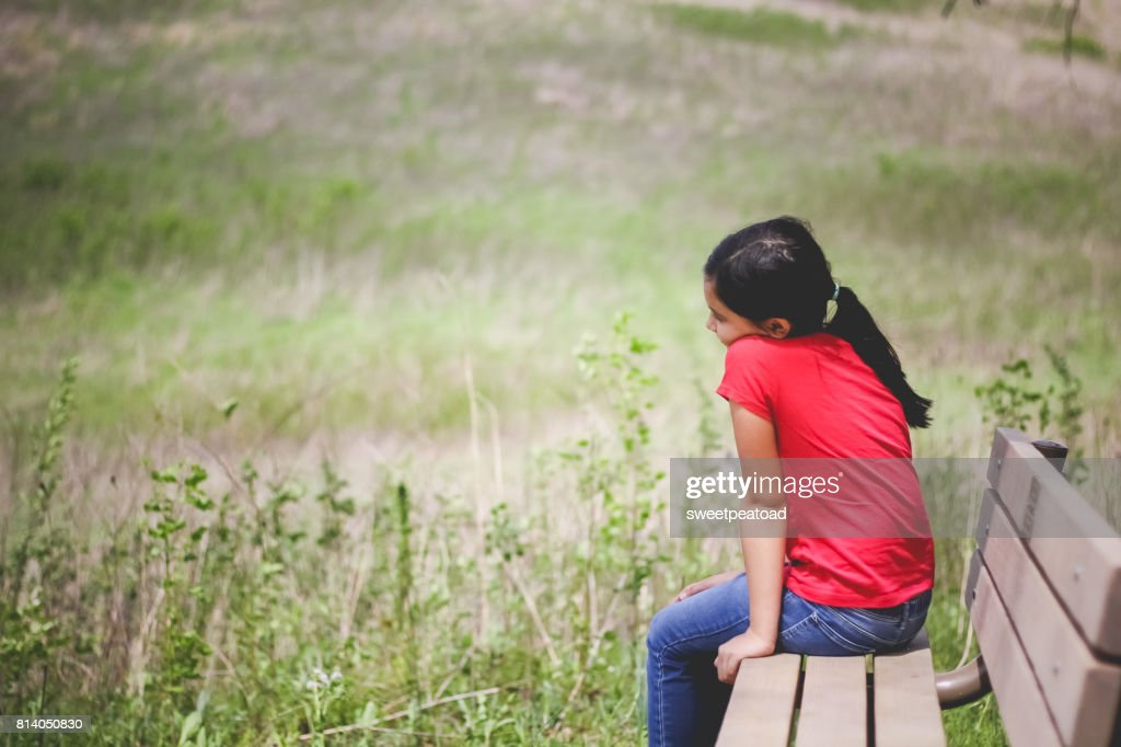 Girl sitting on the bench : Stock Photo