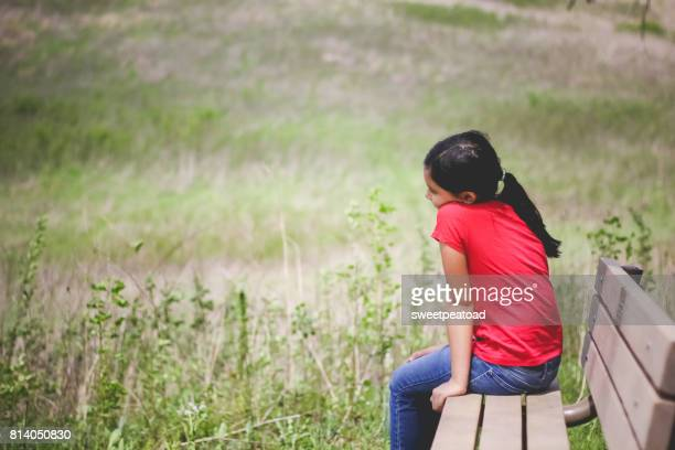 girl sitting on the bench - girl blowing horse - fotografias e filmes do acervo