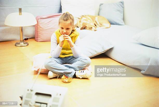 girl sitting on the floor and watching television - dog eats out girl stock pictures, royalty-free photos & images