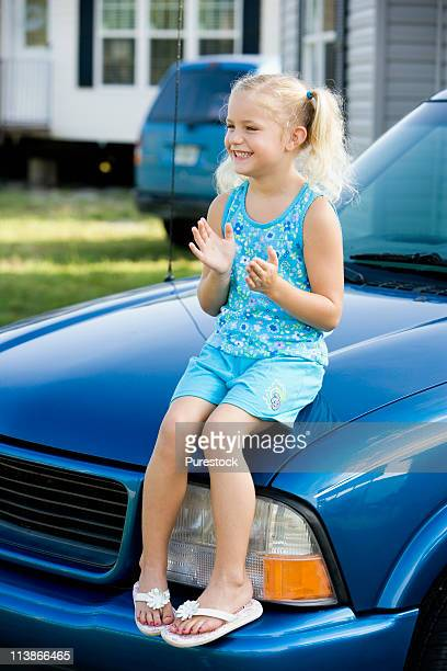 A girl sitting on the hood of a pickup truck