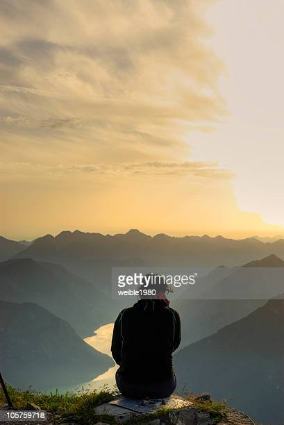 Girl sitting on the top of a mountain