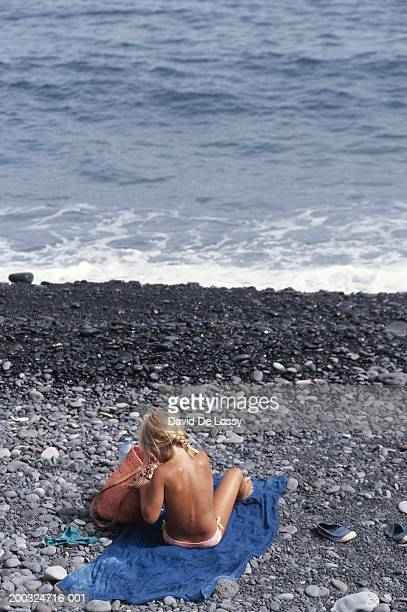 Girl sitting on towel at pebble beach, rear view
