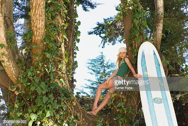 Girl (12-13) sitting on tree with surfboard, low angle view