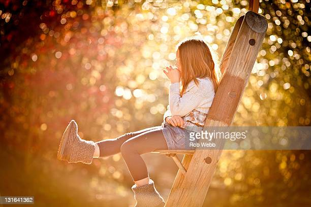 Girl sitting on treehouse seat