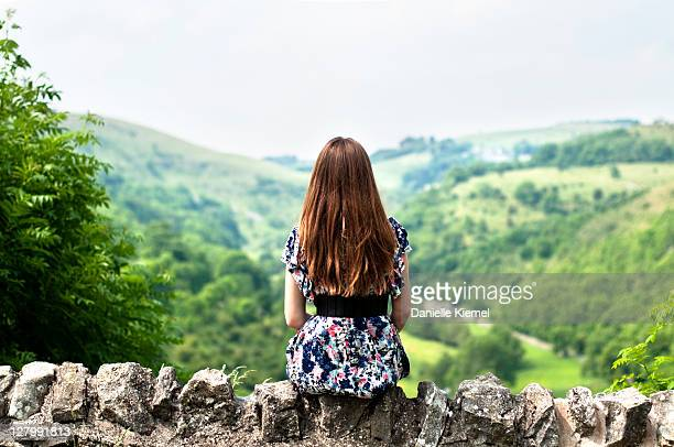 Girl sitting on wall overlooking valley