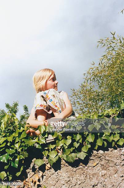 girl sitting on wall - leander licht stock-fotos und bilder