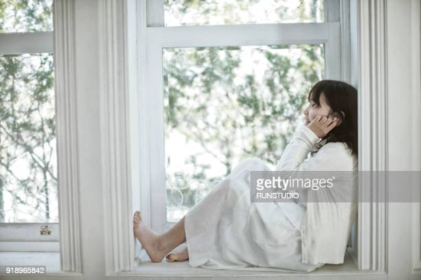 Girl sitting on windowsill listening to music