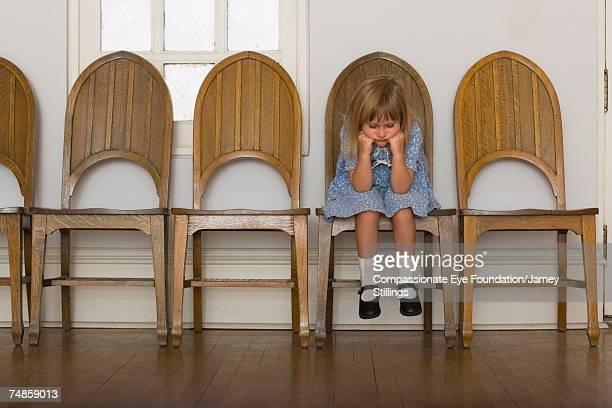 Girl (6-7) sitting on wooden chair in corridor
