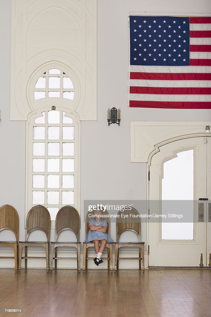 Girl (6-7) sitting on wooden chair in room with American flag : Stock Photo