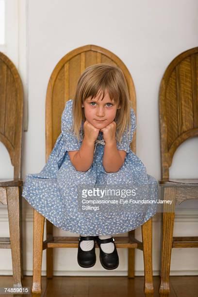 Girl (6-7) sitting on wooden chair, portrait