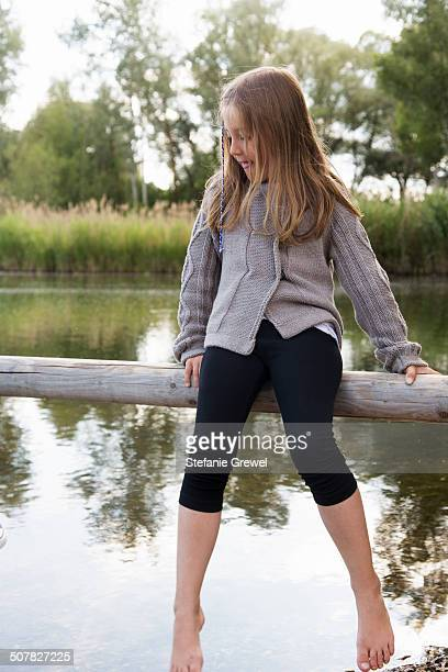 Girl sitting on wooden fence looking down at lake