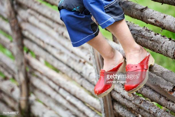 Girl sitting on wooden fence, low section