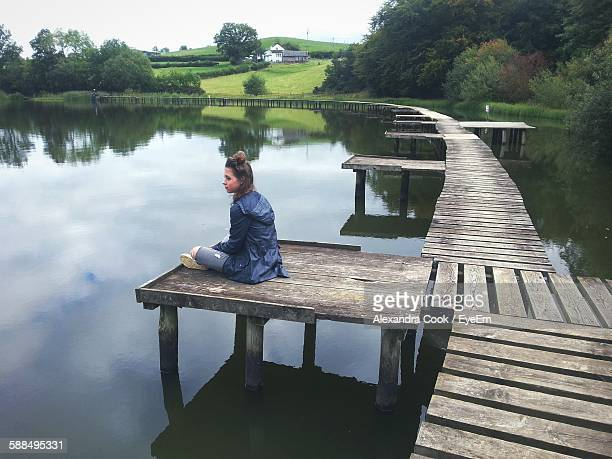 Girl Sitting On Wooden Pier Over Lake
