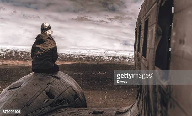 girl sitting on wrecked aircraft engine us navy douglas super dc-3 facing snow capped mountains - airplane crash stock pictures, royalty-free photos & images