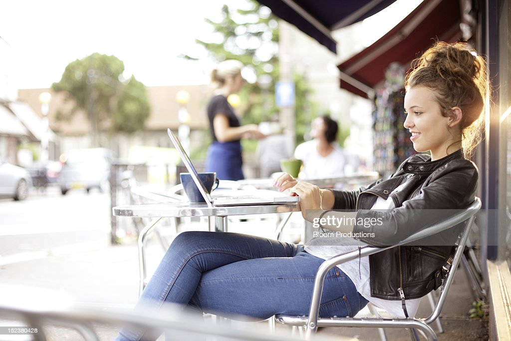 girl sitting outside a cafe using technology : Foto de stock