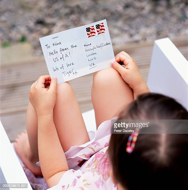 Girl (3-5) sitting reading postcard, close up, elevated view