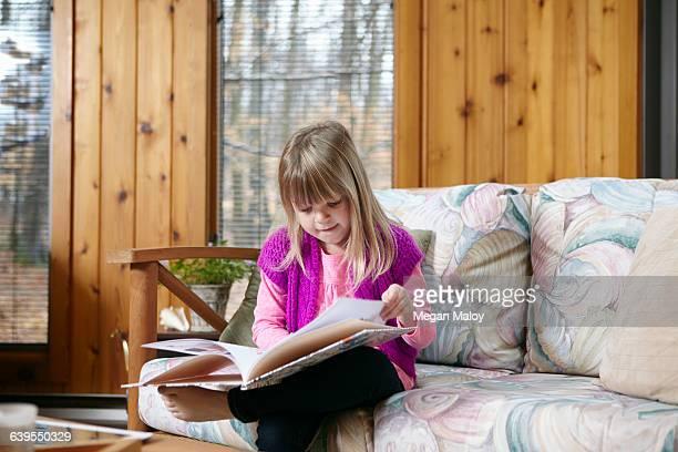 Girl sitting reading story book on living room sofa