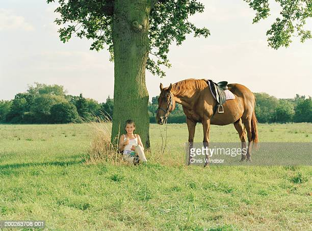 Girl (11-13) sitting under tree eating lunch, by horse, smiling