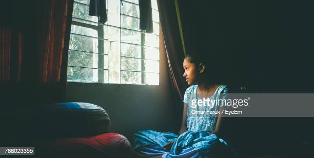 Girl Sitting While Looking Outside Through Window