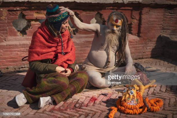 girl sitting with buddhist in pashupatinath - pashupatinath stock pictures, royalty-free photos & images