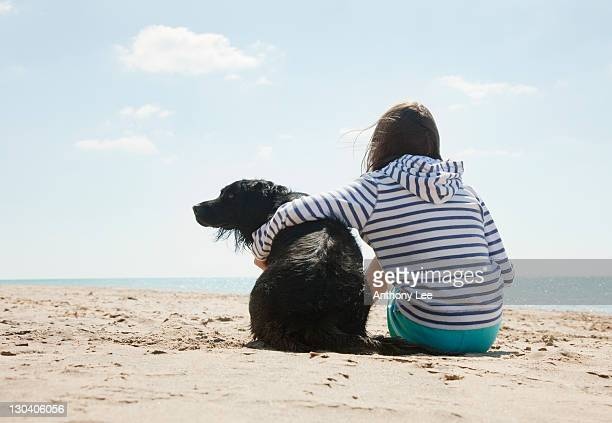 Girl sitting with dog on beach