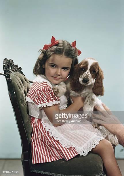 の女の子に座っている笑顔の犬の椅子、