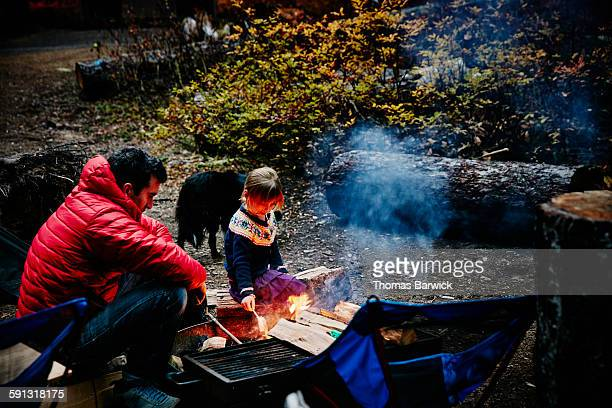Girl sitting with father near fire while camping