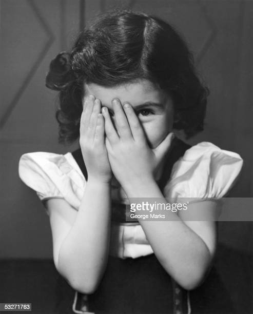 Girl sitting with hands covering right eye