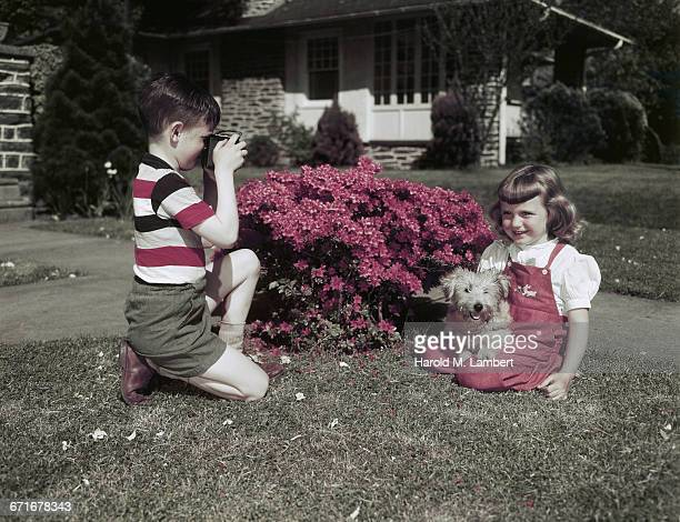 girl sitting with puppy while boy capturing an image  - pawed mammal stock pictures, royalty-free photos & images