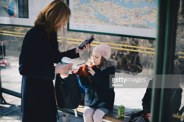 Girl sitting with sister on bench while mother carrying disposable cup and mobile phone at bus stop