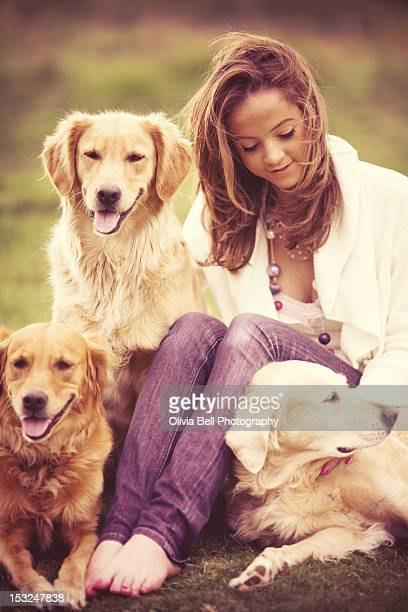 Girl sitting with three golden retrievers