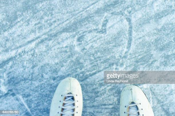 girl skate top view on an outdoor skating rink with a heart shape drawn on ice - ice rink stock photos and pictures