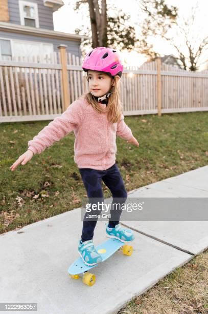 girl skateboarding down on sidewalk - montclair stockfoto's en -beelden