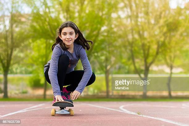 girl skateboarding in park - kind vor der pubertät stock-fotos und bilder