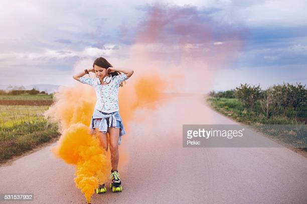 Girl skating surrounded with orange colored smoke grenade