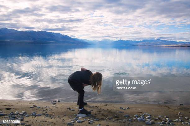 Girl skimming stones at Lake Pukaki, Mount Cook